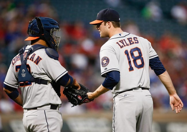 Sep 23, 2013; Arlington, TX, USA; Houston Astros starting pitcher Jordan Lyles (18) and catcher Carlos Corporan (22) meet for a conference against the Texas Rangers during the first inning of a baseball game at Rangers Ballpark in Arlington. Mandatory Credit: Jim Cowsert-USA TODAY Sports