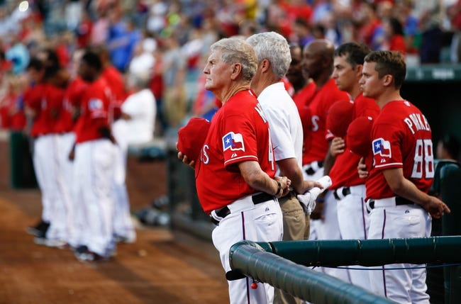 Sep 23, 2013; Arlington, TX, USA; Texas Rangers bench coach Jackie Moore (4) and teammates stand in honor of the National Anthem before their game against the Houston Astros at Rangers Ballpark in Arlington. Mandatory Credit: Jim Cowsert-USA TODAY Sports