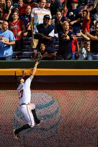 Sep 23, 2013; Atlanta, GA, USA; Atlanta Braves center fielder Jordan Schafer (17) attempts to catch a Milwaukee Brewers catcher Jonathan Lucroy (20) home run in the fifth inning at Turner Field. Mandatory Credit: Daniel Shirey-USA TODAY Sports