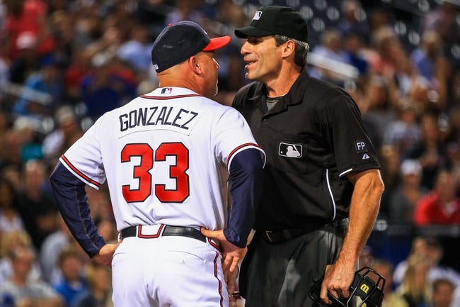 Sep 23, 2013; Atlanta, GA, USA; Atlanta Braves manager Fredi Gonzalez (33) argues a call with home plate umpire Angel Ramirez (55) in the seventh inning against the Milwaukee Brewers at Turner Field. Mandatory Credit: Daniel Shirey-USA TODAY Sports