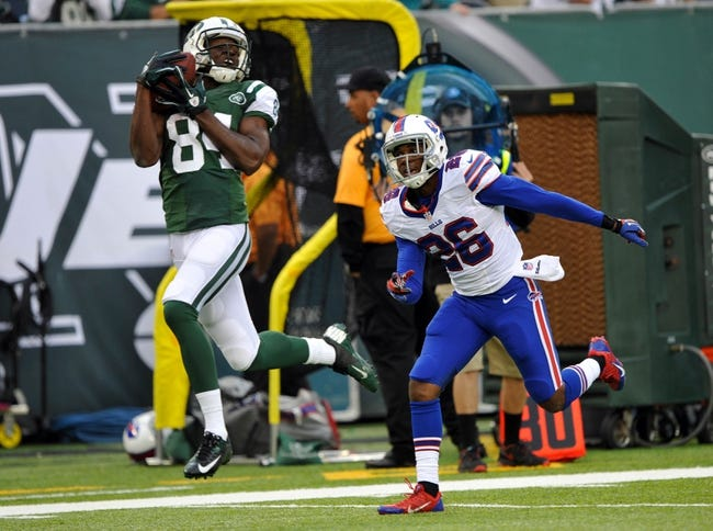 Sep 22, 2013; East Rutherford, NJ, USA; New York Jets wide receiver Stephen Hill (84) catches a pass for a touchdown over Buffalo Bills defensive back Justin Rogers (26) at MetLife Stadium. Mandatory Credit: Robert Deutsch-USA TODAY Sports
