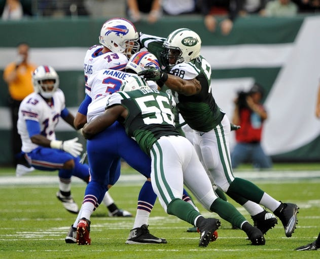 Sep 22, 2013; East Rutherford, NJ, USA; New York Jets inside linebacker DeMario Davis (56) and New York Jets linebacker Quinton Coples (98) sack Buffalo Bills quarterback EJ Manuel (3) during the second quarter at MetLife Stadium. Mandatory Credit: Robert Deutsch-USA TODAY Sports