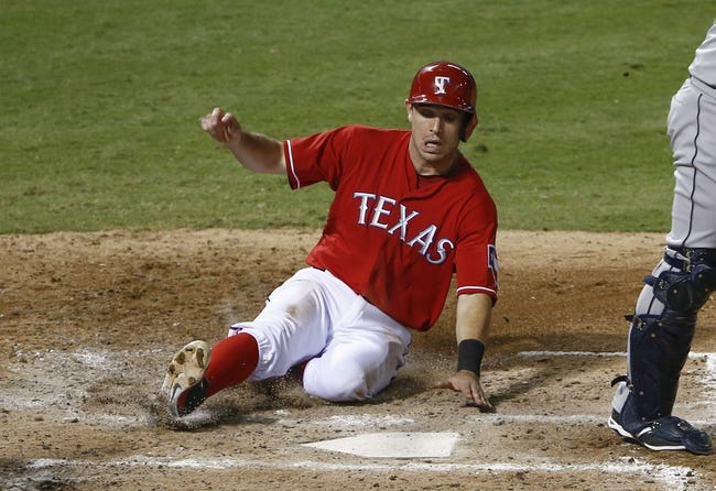 Sep 23, 2013; Arlington, TX, USA; Texas Rangers second baseman Ian Kinsler (5) slides home ahead of the throw to Houston Astros catcher Carlos Corporan (22) on a single by shortstop Elvis Andrus (not shown) during the fourth inning of a baseball game at Rangers Ballpark in Arlington. Mandatory Credit: Jim Cowsert-USA TODAY Sports
