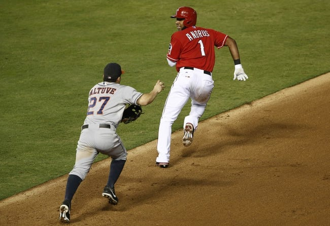 Sep 23, 2013; Arlington, TX, USA; Texas Rangers shortstop Elvis Andrus (1) is chased down by Houston Astros second baseman Jose Altuve (27) after attempting to stretch a single into a double during the fourth inning of a baseball game at Rangers Ballpark in Arlington. Mandatory Credit: Jim Cowsert-USA TODAY Sports