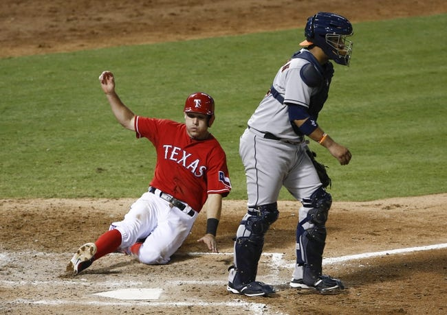 Sep 23, 2013; Arlington, TX, USA; Texas Rangers second baseman Ian Kinsler (5) slides home ahead of the throw to Houston Astros catcher Carlos Corporan (22) during the fourth inning of a baseball game at Rangers Ballpark in Arlington. Mandatory Credit: Jim Cowsert-USA TODAY Sports