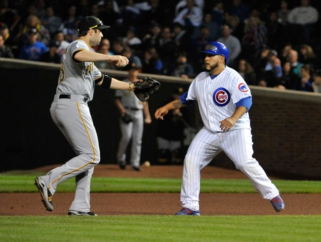 Sep 23, 2013; Chicago, IL, USA; Chicago Cubs catcher Dioner Navarro (30) avoids a tag by Pittsburgh Pirates second baseman Neil Walker (18) during the seventh inning at Wrigley Field. Mandatory Credit: David Banks-USA TODAY Sports