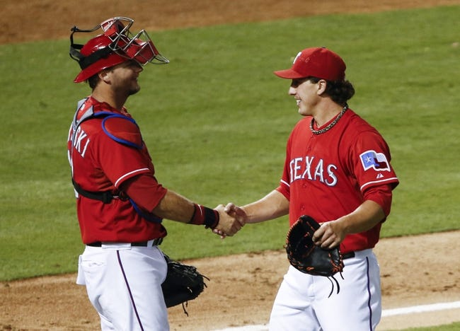 Sep 23, 2013; Arlington, TX, USA; Texas Rangers starting pitcher Derek Holland (right) and catcher A.J. Pierzynski (left) congratulate each other after their win against the  a baseball game at Rangers Ballpark in Arlington. Holland pitched nine innings of shut-out baseball beating the Astros 12-0. Mandatory Credit: Jim Cowsert-USA TODAY Sports
