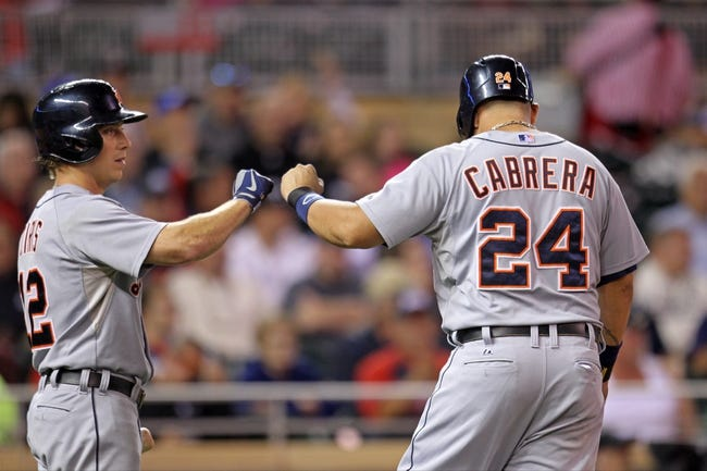 Sep 23, 2013; Minneapolis, MN, USA; Detroit Tigers third baseman Miguel Cabrera (24) is congratulated by outfielder Andy Dirks (12) after scoring a run during the seventh inning against the Minnesota Twins at Target Field. Mandatory Credit: Brace Hemmelgarn-USA TODAY Sports