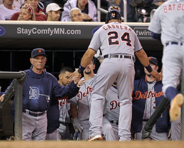 Sep 23, 2013; Minneapolis, MN, USA; Detroit Tigers third baseman Miguel Cabrera (24) is congratulated by teammates after scoring a run during the seventh inning against the Minnesota Twins at Target Field. Mandatory Credit: Brace Hemmelgarn-USA TODAY Sports