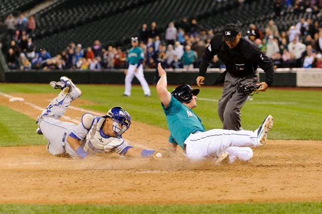 Sep 23, 2013; Seattle, WA, USA; Seattle Mariners third baseman Kyle Seager (15) is tagged out by Kansas City Royals catcher Salvador Perez (13) at home plate during the 10th inning at Safeco Field. Mandatory Credit: Steven Bisig-USA TODAY Sports