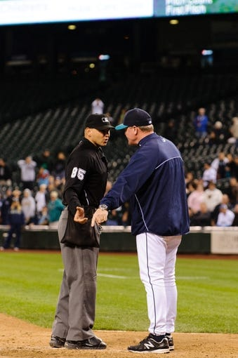 Sep 23, 2013; Seattle, WA, USA; Seattle Mariners manager Eric Wedge (22) argues with home plate umpire Vic Carapazza (85) after Carapazza  called Seattle Mariners third baseman Kyle Seager (15) (not pictured) out at home plate during the 10th inning at Safeco Field. Mandatory Credit: Steven Bisig-USA TODAY Sports