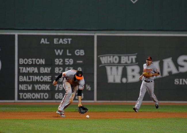 Sep 17, 2013; Boston, MA, USA; Baltimore Orioles third baseman Manny Machado (13) fields a ground ball during the first inning against the Boston Red Sox at Fenway Park. Mandatory Credit: Bob DeChiara-USA TODAY Sports