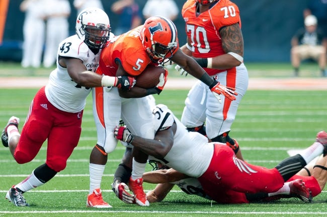 Sep 7, 2013; Champaign, IL, USA; Illinois Fighting Illini running back Donovonn Young (5) is tackled by Cincinnati Bearcats linebacker Nick Temple (43) and Cincinnati Bearcats linebacker Greg Blair (51) at Memorial Stadium. Mandatory Credit: Bradley Leeb-USA TODAY Sports