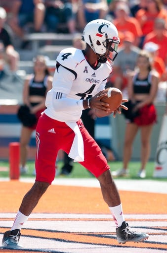 Sep 7, 2013; Champaign, IL, USA; Cincinnati Bearcats quarterback Munchie Legaux (4) hands the ball off during the game against the Illinois Fighting Illini at Memorial Stadium. Mandatory Credit: Bradley Leeb-USA TODAY Sports
