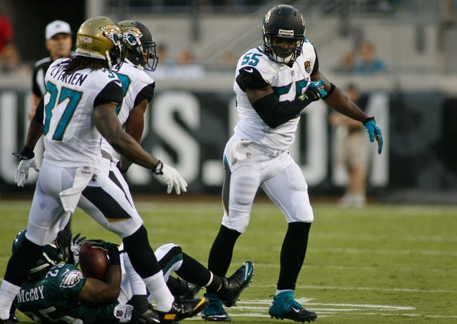 Aug 24, 2013; Jacksonville, FL, USA; At right, Jacksonville Jaguars linebacker Geno Hayes (55) reacts after a tackle on Philadelphia Eagles running back LeSean McCoy (25) in the first quarter of their game at EverBank Field. The Philadelphia Eagles beat the Jacksonville Jaguars 31-24. Mandatory Credit: Phil Sears-USA TODAY Sports