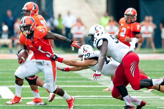 Sep 7, 2013; Champaign, IL, USA; Illinois Fighting Illini running back Donovonn Young (5) avoids a tackle by Cincinnati Bearcats safety Andre Jones (29) at Memorial Stadium. Mandatory Credit: Bradley Leeb-USA TODAY Sports
