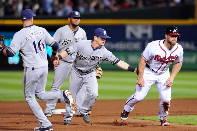 Sep 24, 2013; Atlanta, GA, USA; Atlanta Braves left fielder Evan Gattis (24) gets tagged out by Milwaukee Brewers second baseman Scooter Gennett (2) after a run down during the fourth inning at Turner Field. Mandatory Credit: Dale Zanine-USA TODAY Sports