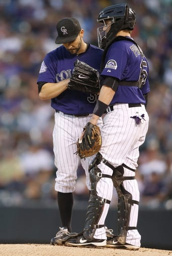 Sep 24, 2013; Denver, CO, USA; Colorado Rockies pitcher Tyler Chatwood (left) and catcher Jordan Pacheco (right) chat on the mound during the first inning against the Boston Red Sox at Coors Field. Mandatory Credit: Chris Humphreys-USA TODAY Sports