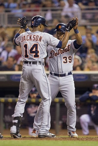 Sep 24, 2013; Minneapolis, MN, USA; Detroit Tigers center fielder Austin Jackson (14) celebrates with second baseman Ramon Santiago (39) after hitting a home run in the fourth inning against the Minnesota Twins at Target Field. Mandatory Credit: Jesse Johnson-USA TODAY Sports