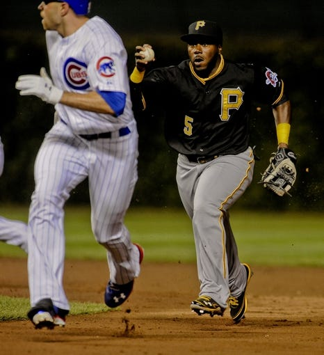 Sep 24, 2013; Chicago, IL, USA;  Pittsburgh Pirates infielder Josh Harrison chases down Chicago Cubs outfielder Nate Schierholtz in between first and second base in the second inning at Wrigley Field. Mandatory Credit: Matt Marton-USA TODAY Sports