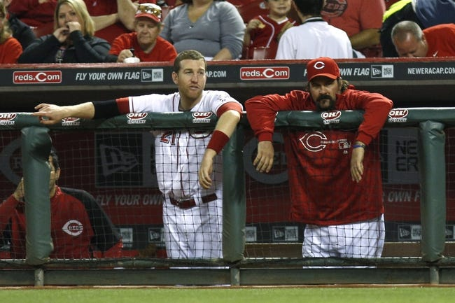 Sep 24, 2013; Cincinnati, OH, USA; Cincinnati Reds third baseman Todd Frazier, left, and Cincinnati Reds catcher Corky Miller, right, watch from the dugout during a game against the New York Mets at Great American Ball Park. Mandatory Credit: David Kohl-USA TODAY Sports