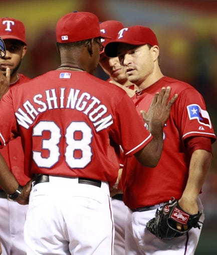 Sep 24, 2013; Arlington, TX, USA; Texas Rangers manager Ron Washington (38) talks with pitcher relief pitcher Jason Frasor (44) on the mound during the game against the Houston Astros at Rangers Ballpark in Arlington. The Texas Rangers beat the Houston Astros 3-2. Mandatory Credit: Tim Heitman-USA TODAY Sports