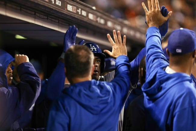 Sep 24, 2013; San Francisco, CA, USA; Los Angeles Dodgers right fielder Yasiel Puig (66) high fives teammates in the dugout after hitting a solo home run against the San Francisco Giants during the fifth inning at AT&T Park. Mandatory Credit: Kelley L Cox-USA TODAY Sports