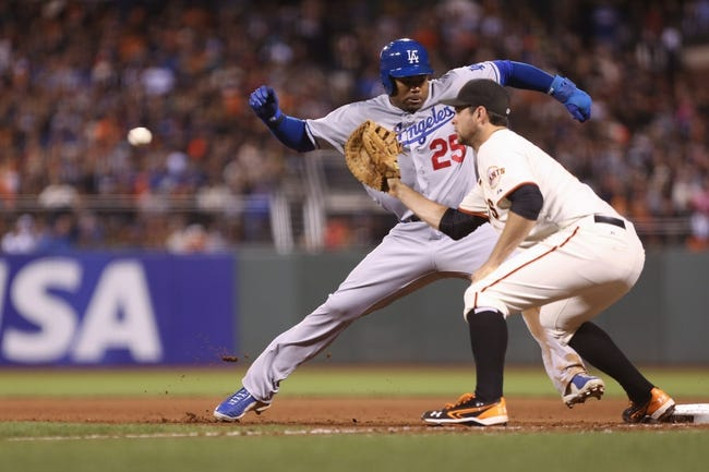 Sep 24, 2013; San Francisco, CA, USA; Los Angeles Dodgers left fielder Carl Crawford (25) jumps safely back to first base against San Francisco Giants first baseman Brandon Belt (9) during the seventh inning at AT&T Park. Mandatory Credit: Kelley L Cox-USA TODAY Sports