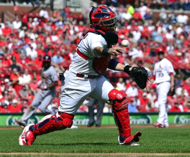 Sep 25, 2013; St. Louis, MO, USA; St. Louis Cardinals catcher Yadier Molina (4) throws out a Washington Nationals base runner at Busch Stadium. The Cardinals defeated the Nationals 4-1. Mandatory Credit: Scott Rovak-USA TODAY Sports