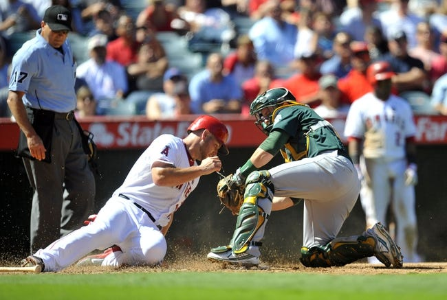 September 25, 2013; Anaheim, CA, USA; Los Angeles Angels catcher Chris Iannetta (17) is out at home plate against the tag of Oakland Athletics catcher Stephen Vogt (21) in the fifth inning at Angel Stadium of Anaheim. Mandatory Credit: Gary A. Vasquez-USA TODAY Sports