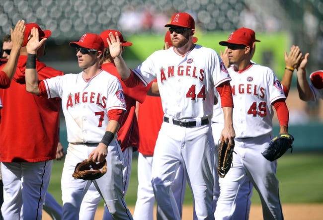 September 25, 2013; Anaheim, CA, USA; Los Angeles Angels first baseman Mark Trumbo (44), shortstop Andrew Romine (7) celebrate the 3-1 victory against the Oakland Athletics at Angel Stadium of Anaheim. Mandatory Credit: Gary A. Vasquez-USA TODAY Sports