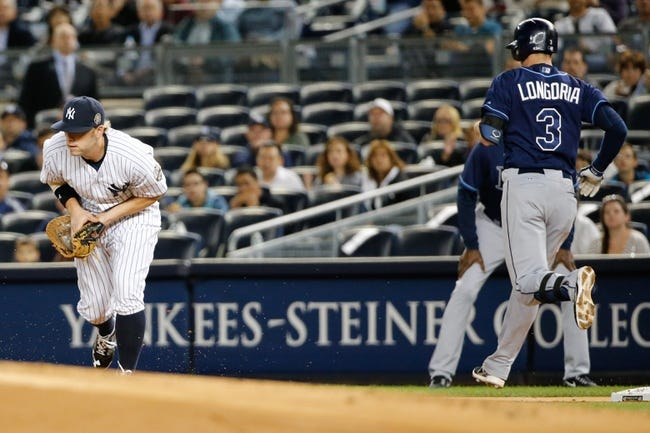 Sep 25, 2013; Bronx, NY, USA;  Tampa Bay Rays third baseman Evan Longoria (3) goes to first as New York Yankees first baseman Mark Reynolds (39) fails to make the tag during the first inning Yankee Stadium. Mandatory Credit: Anthony Gruppuso-USA TODAY Sports