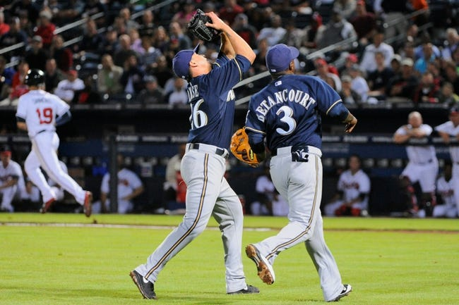 Sep 25, 2013; Atlanta, GA, USA; Milwaukee Brewers starting pitcher Kyle Lohse (26) catches a pop up next to third baseman Yuniesky Betancourt (3) against the Atlanta Braves during the sixth inning at Turner Field. Mandatory Credit: Dale Zanine-USA TODAY Sports