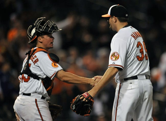 Sep 25, 2013; Baltimore, MD, USA; Baltimore Orioles catcher Steve Clevenger (45) congratulates pitcher Jason Hammel (39) after a game against the Toronto Blue Jays at Oriole Park at Camden Yards. The Orioles defeated the Blue Jays 9-5. Mandatory Credit: Joy R. Absalon-USA TODAY Sports