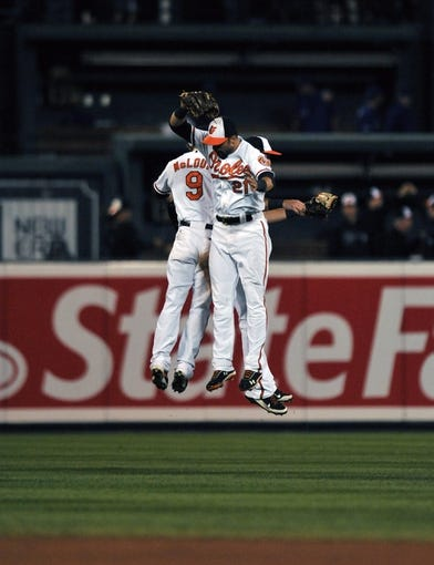 Sep 25, 2013; Baltimore, MD, USA; Baltimore Orioles teammates Nate McLouth (left) Nick Markakis (right) and Jason Pridie (back) celebrate after a game against the Toronto Blue Jays at Oriole Park at Camden Yards. The Orioles defeated the Blue Jays 9-5. Mandatory Credit: Joy R. Absalon-USA TODAY Sports