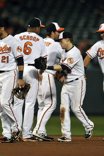 Sep 25, 2013; Baltimore, MD, USA; Baltimore Orioles teammates Jonathan Schoop (left) and Nate McLouth (right) celebrate after a game against the Toronto Blue Jays at Oriole Park at Camden Yards. The Orioles defeated the Blue Jays 9-5. Mandatory Credit: Joy R. Absalon-USA TODAY Sports