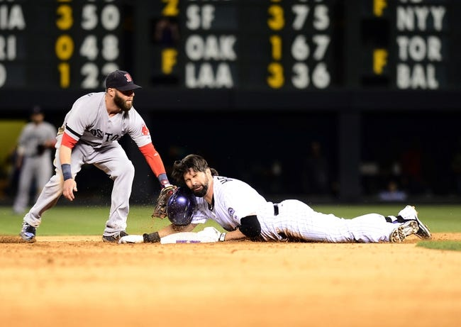 Sep 25, 2013; Denver, CO, USA; Boston Red Sox second baseman Dustin Pedroia (15) attempts to tag out Colorado Rockies first baseman Todd Helton (17)  after hitting a double in the fifth inning of the game against the Boston Red Sox at Coors Field. Mandatory Credit: Ron Chenoy-USA TODAY Sports