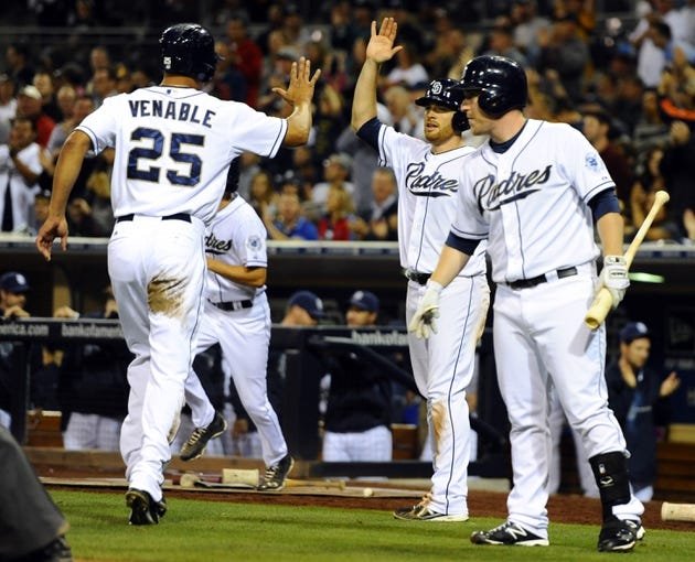 Sep 25, 2013; San Diego, CA, USA; San Diego Padres right fielder Will Venable (25) is congratulated by starting pitcher Ian Kennedy (center) and second baseman Jedd Gyorko (right) after scoring during the fifth inning against the Arizona Diamondbacks at Petco Park. Mandatory Credit: Christopher Hanewinckel-USA TODAY Sports