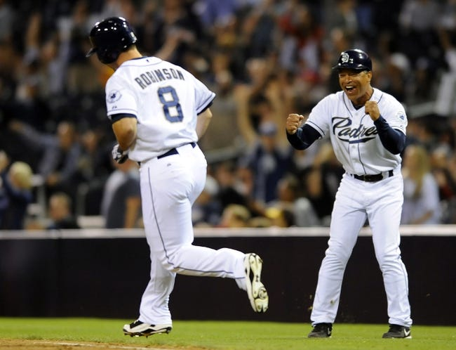 Sep 25, 2013; San Diego, CA, USA; San Diego Padres first base coach Dave Roberts (right) cheers as pinch hitter Chris Robinson (8) runs the bases following his first major league hit, a home run in the eighth inning, against the Arizona Diamondbacks at Petco Park. Mandatory Credit: Christopher Hanewinckel-USA TODAY Sports