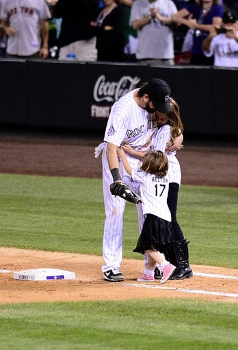 Sep 25, 2013; Denver, CO, USA; Colorado Rockies first baseman Todd Helton (17) is joined by daughters Tierney Faith (right) and Gentry Grace (left) at the top of the ninth inning against the Boston Red Sox at Coors Field. The Red Sox defeated the Rockies 15-5. Mandatory Credit: Ron Chenoy-USA TODAY Sports