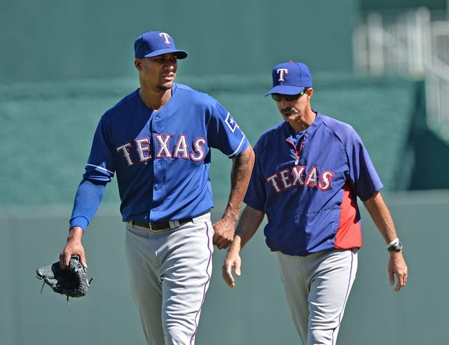 Sep 22, 2013; Kansas City, MO, USA; Texas Rangers pitcher Alexi Ogando (left) walks out of the bullpen with pitching coach Mike Maddux (right) against the Kansas City Royals before the game at Kauffman Stadium. Mandatory Credit: Peter G. Aiken-USA TODAY Sports