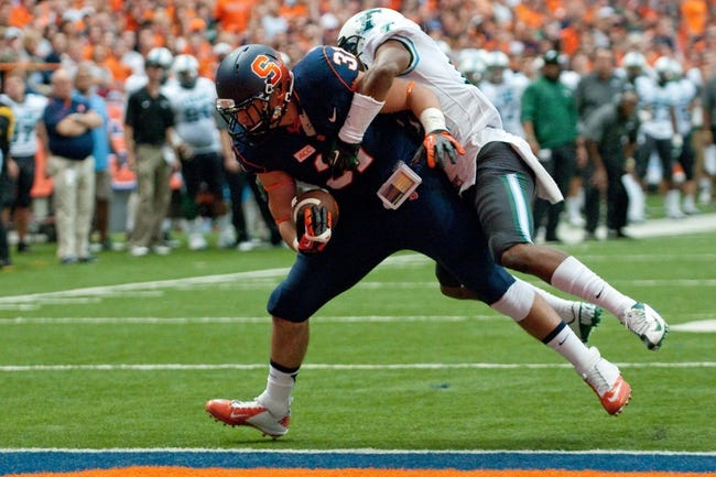 Sep 21, 2013; Syracuse, NY, USA; Syracuse Orange fullback Clay Cleveland (31) scores a touchdown over Tulane Green Wave cornerback Jordan Batiste (14) in the third quarter of a game at Carrier Dome. Syracuse won the game 52-17. Mandatory Credit: Mark Konezny-USA TODAY Sports