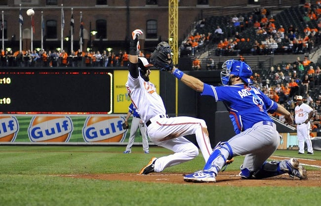 Sep 26, 2013; Baltimore, MD, USA; Baltimore Orioles right fielder Nick Markakis (21) is safe at home on a one-run rbi sac fly by Matt Wieters (not shown) as Toronto Blue Jays catcher J.P. Arencibia (9) does not get the throw in time at Oriole Park at Camden Yards. Mandatory Credit: Joy R. Absalon-USA TODAY Sports