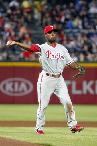 Sep 26, 2013; Atlanta, GA, USA; Philadelphia Phillies shortstop Jimmy Rollins (11) throws a runner out at first against the Atlanta Braves in the fourth inning at Turner Field. Mandatory Credit: Brett Davis-USA TODAY Sports