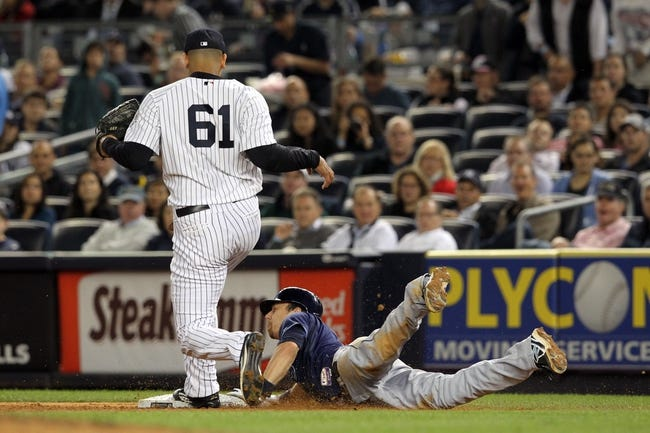 Sep 26, 2013; Bronx, NY, USA; New York Yankees relief pitcher Dellin Betances (61) fails to cover first base on a ball hit by Tampa Bay Rays second baseman Ben Zobrist (18) during the eighth inning of a game at Yankee Stadium. Zobrist was safe at first. Mandatory Credit: Brad Penner-USA TODAY Sports