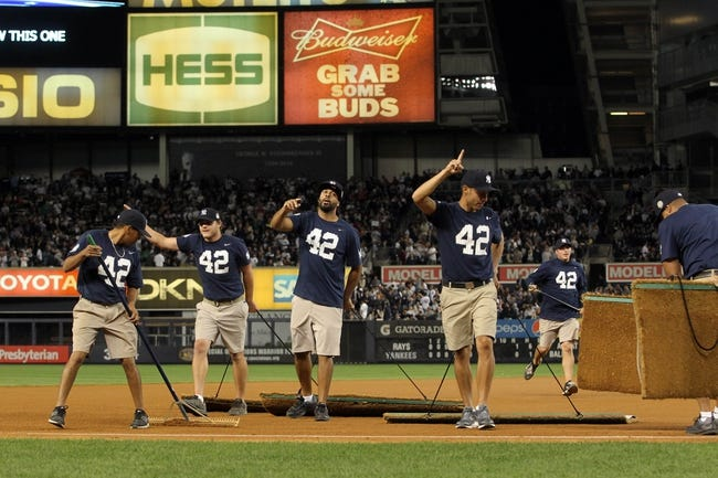 Sep 26, 2013; Bronx, NY, USA; Yankee Stadium grounds crew wear 42 to honor New York Yankees relief pitcher Mariano Rivera (not pictured) as they groom the field during the sixth inning of a game against the Tampa Bay Rays at Yankee Stadium. Mandatory Credit: Brad Penner-USA TODAY Sports