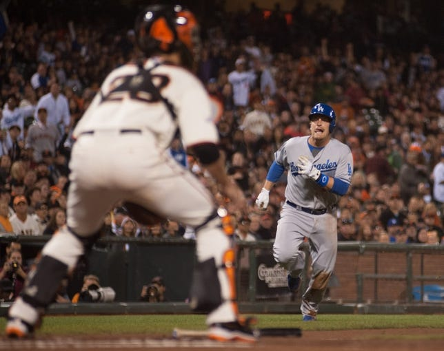 Sep 26, 2013; San Francisco, CA, USA; Los Angeles Dodgers catcher Tim Federowicz (18) attempts to score from second base as San Francisco Giants catcher Buster Posey (28) prepares for a play at the plate during the second inning at AT&T Park. Mandatory Credit: Ed Szczepanski-USA TODAY Sports