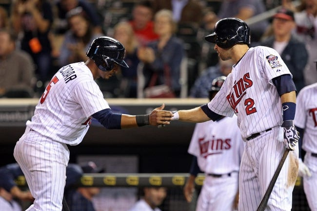 Sep 26, 2013; Minneapolis, MN, USA; Minnesota Twins shortstop Eduardo Escobar (5) celebrates with third baseman Trevor Plouffe (24) after scoring a run in the ninth inning against the Cleveland Indians at Target Field. The Indians won 6-5. Mandatory Credit: Jesse Johnson-USA TODAY Sports