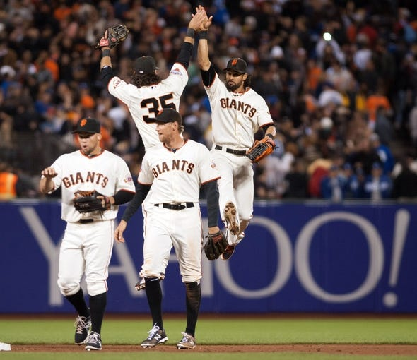 Sep 26, 2013; San Francisco, CA, USA; San Francisco Giants shortstop Brandon Crawford (35) and center fielder Angel Pagan (16) celebrate after defeating the Los Angeles Dodgers at AT&T Park. The San Francisco Giants defeated the Los Angeles Dodgers 3-2. Mandatory Credit: Ed Szczepanski-USA TODAY Sports