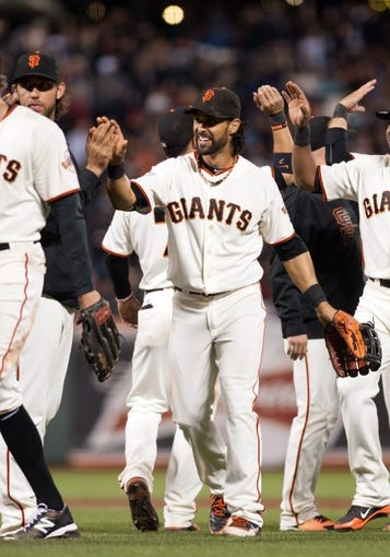 Sep 26, 2013; San Francisco, CA, USA; San Francisco Giants center fielder Angel Pagan (16) high fives team mates after defeating the Los Angeles Dodgers at AT&T Park. The San Francisco Giants defeated the Los Angeles Dodgers 3-2. Mandatory Credit: Ed Szczepanski-USA TODAY Sports